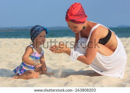 Young mother playing with daughter on the beach dressed in colorful kerchiefs  view 3 - stock photo