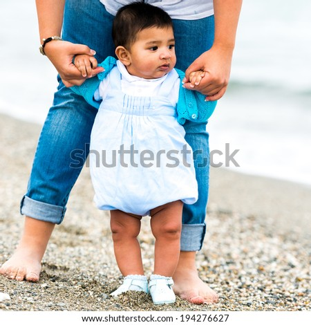 young mother playing with her baby boy on the beach on a sunny  day - stock photo