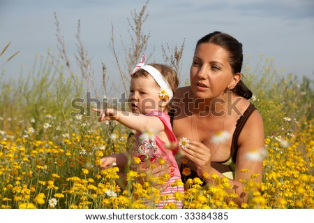Young mother playing with her baby girl on beautiful colorful meadow - stock photo