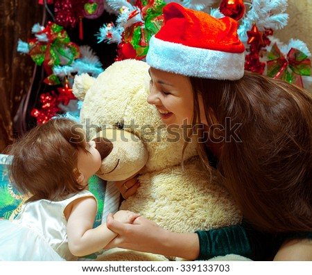 Young mother playing with her daughter and teddy bear under the Christmas tree in the Santa hats. Christmas mood, New year. - stock photo