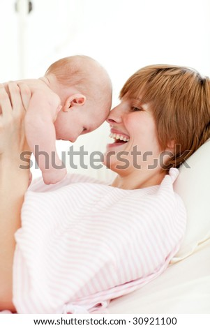 Young mother playing with her newborn baby - stock photo