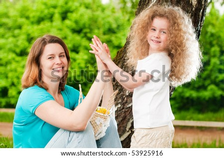 young mother playing with her small daughter in park on green grass, both happy and smiling - stock photo