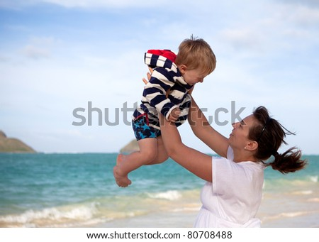 Young mother playing with her son on a tropical beach - stock photo