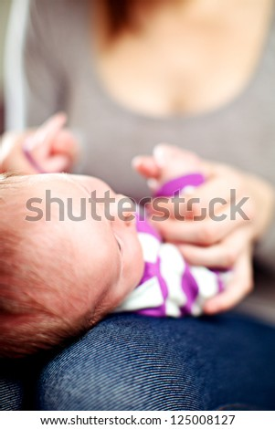 Young mother playing with her tiny baby holding its hands as it lies on her lap - stock photo