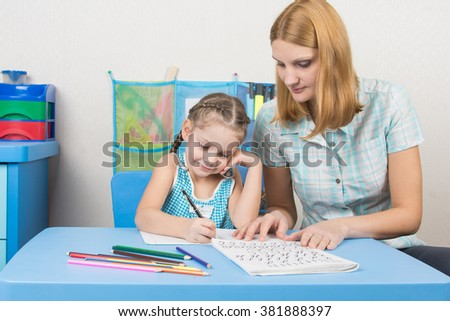 Young mother prepares a five-year girl to school - stock photo