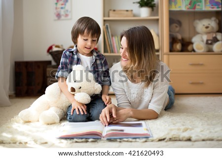 Young mother, read a book to her child, boy in the living room of their home, rays of sun going through the window - stock photo
