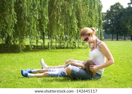 Young mother relaxing with her son in a park - stock photo