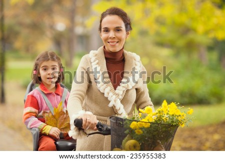 Young mother riding a bicycle with her daughter on a back seat - stock photo