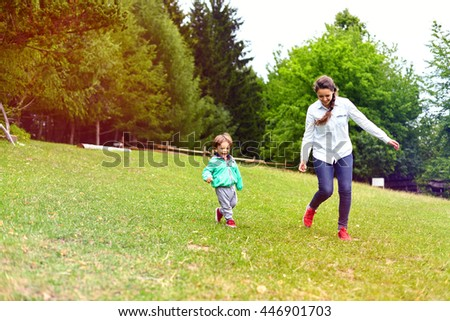 Young mother running with little boy on sunny day in the park. Happy woman and adorable toddler child having fun. Motherhood and childhood concept, positive human emotions, feelings. - stock photo