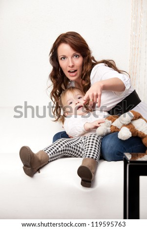 Young mother showing on something - stock photo