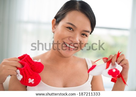 Young mother showing shoes for her future baby - stock photo