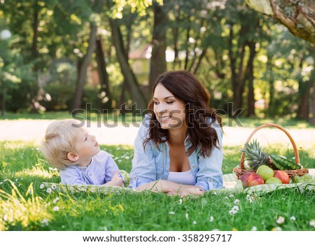 Young mother spending time with her son in the park having a picnic. - stock photo