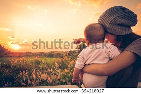 Young mother standing near a river & carrying her baby looking at the beautiful Sunset. Also Seeing a beautiful green field & mountain on a background. Mother pointing her baby see the Sun - stock photo