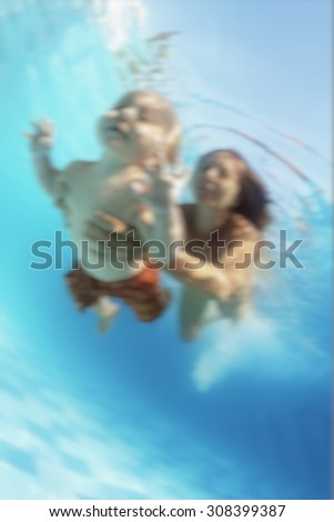 Young mother swimming with fun with happy baby son - dive underwater  with cheerful boy in pool. Healthy family lifestyle and children water sports activity and lessons with parents. Blur background. - stock photo