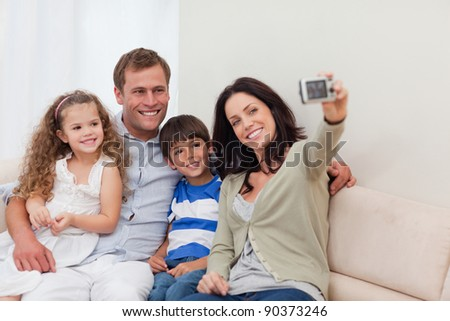 Young mother taking family photograph on the couch - stock photo