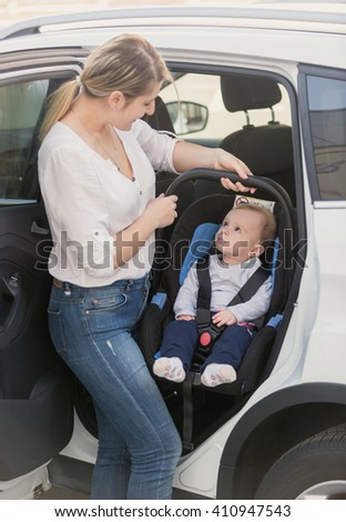 Young mother taking her baby in safety seat out of the car - stock photo