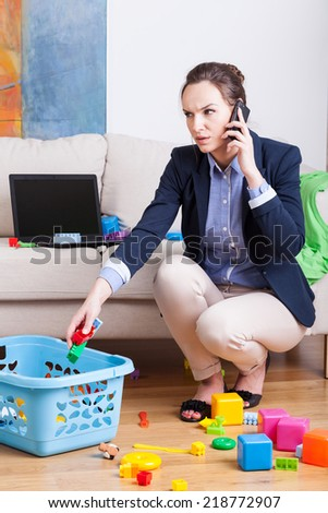 Young mother talking on phone and cleaning up toys - stock photo