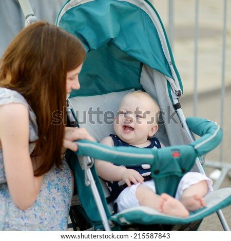 Young mother talking to smiling baby in a stroller - stock photo