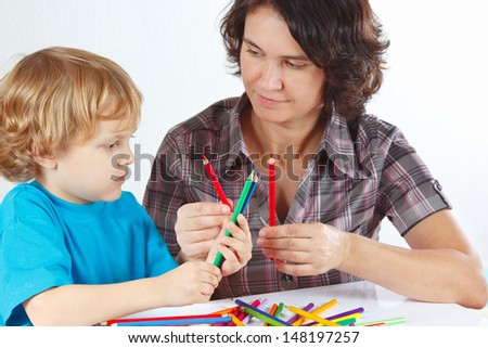 Young mother teaches her child to draw with color pencils on a white background - stock photo