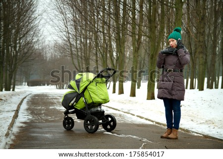 young mother walking with pram in winter park talking on the phone and did not notice as a child stroller rolled - stock photo