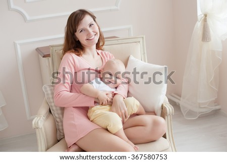 young mother with a child in the bedroom in the morning - stock photo