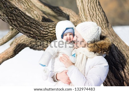 Young mother with a little baby walking in a snowy park - stock photo