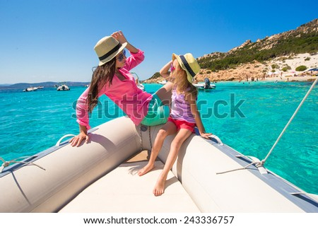Young mother with adorable daughter enjoy vacation on boat - stock photo