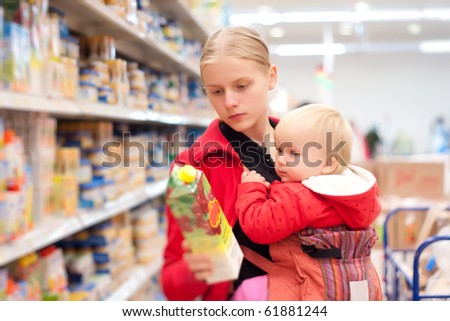 Young mother with baby daughter shopping in supermarket - stock photo