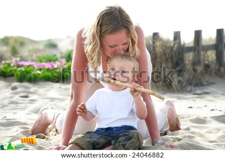 young mother with baby outdoors - bright family lifestyle portrait - stock photo