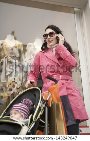 Young mother with baby standing in front of shop using mobile phone - stock photo