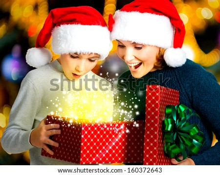 Young mother with  child opens the box with gifts on the christmas holiday - indoors - stock photo