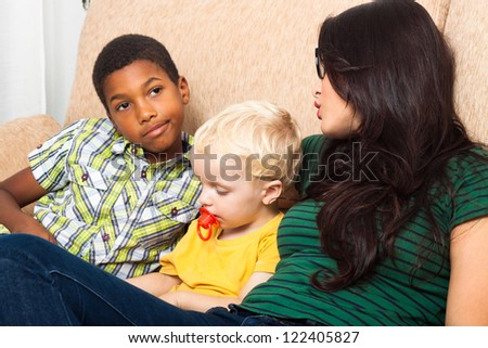 Young mother with children on sofa. - stock photo