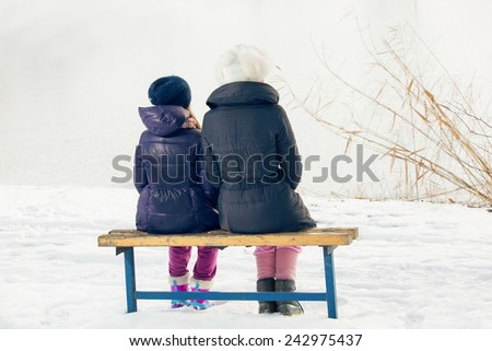 Young mother with her daughter sitting on wooden bench in park. Selective focus - stock photo