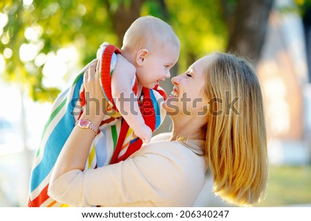 Young mother with her little baby in a sunset  - stock photo
