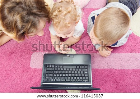 Young mother with her son and daughter lying on floor with laptop. Directly from above view. - stock photo
