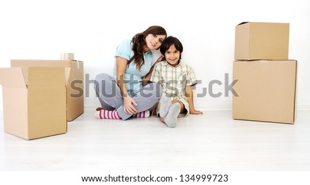 Young mother with her son packing card boxes and moving to new home - stock photo
