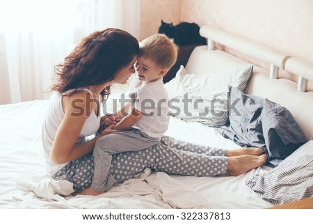 Young mother with her 2 years old little son dressed in pajamas are relaxing and playing in the bed at the weekend together, lazy morning, warm and cozy scene. Pastel colors, selective focus. - stock photo