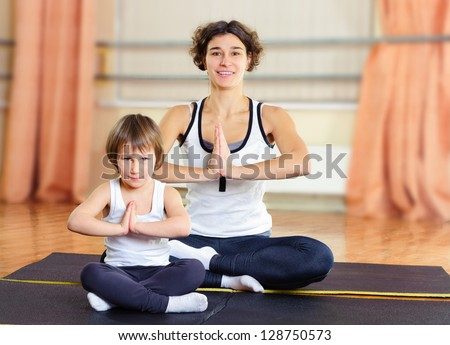 Young mother with little daughter exercising in gym - stock photo