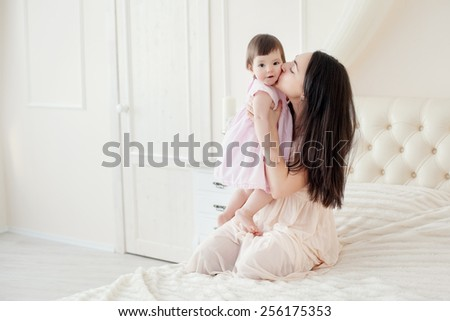 Young mother with little daughter in the bedroom - stock photo