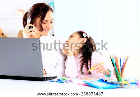 Young mother with little daughter sitting together at home - stock photo