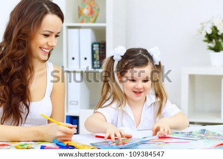 Young mother with little daughter studying at home - stock photo