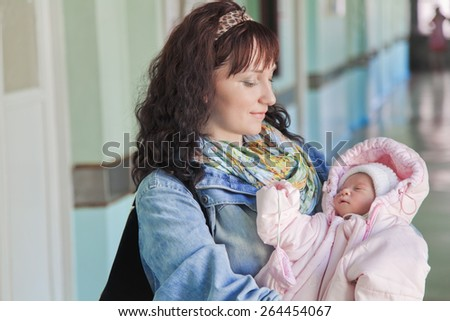 Young mother with newborn baby in hospital at the day of discharge from maternity ward - stock photo