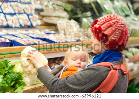 Young mother with toddler girl shopping in supermarket - stock photo