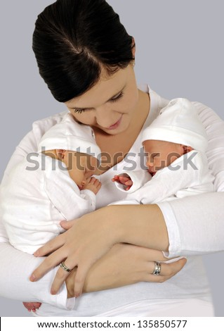 Young mother with twin babies in white clothing - stock photo