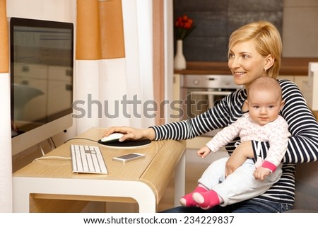 Young mother working on computer while holding baby girl on lap, smiling. - stock photo