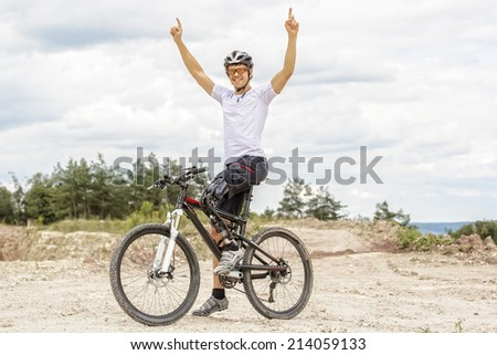 Young  mountain bike rider with leg prosthesis raising up his arms  - stock photo