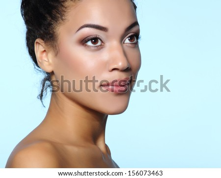 Young mulatto attractive calm woman with beautiful makeup, over blue - stock photo