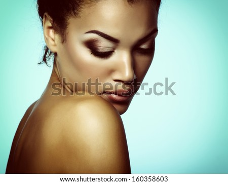 Young mulatto fresh woman with beautiful makeup looking down, isolated on blue, toned - stock photo