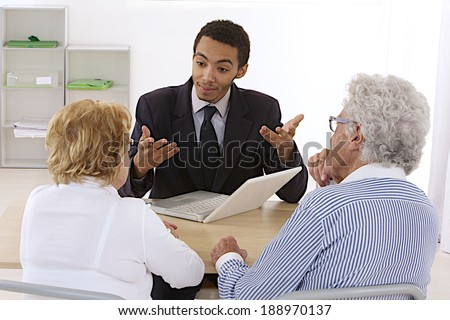 Young mulatto salesman meets with senior couple in his office. Could be real estate, life insurance. - stock photo