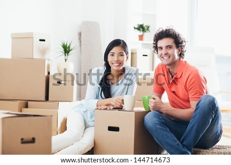 Young multi-ethnic couple having a break while moving into their new home. - stock photo